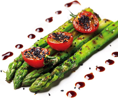 4 Mary Washington asparagus spears aside one another, seasoned with 3 halved cherry tomatoes on top with a dark sauce dotted alongside the asparagus