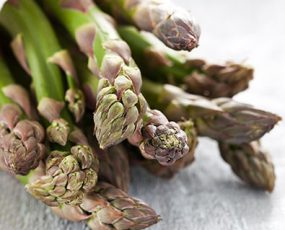 The top portion of a bundle of Jersey Knight Asparagus resting on a wooden surface