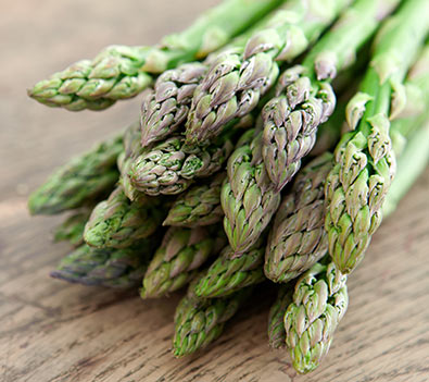 Jersey Knight asparagus tops resting on a wooden surface