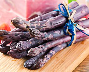 A bundle of 9 Purple Passion asparagus shoots tied with blue and beige paper ribbon atop a bamboo cutting board